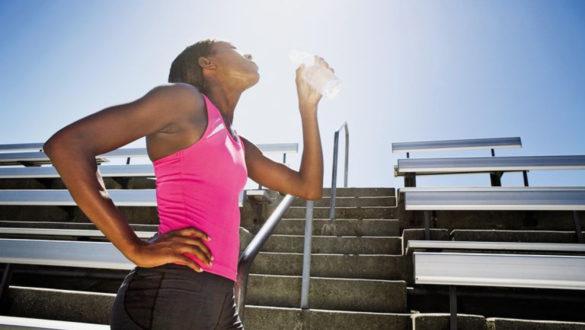 Femme qui bois pendant une séance de running
